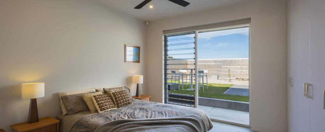 Bespoke home in clayton bay bedroom with door to garden