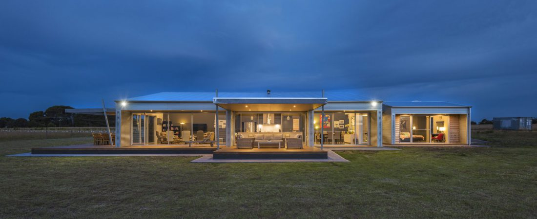 Bespoke home in Clayton bay. Beautiful night time shot with lights on. Custom built glass fronted house in the country.