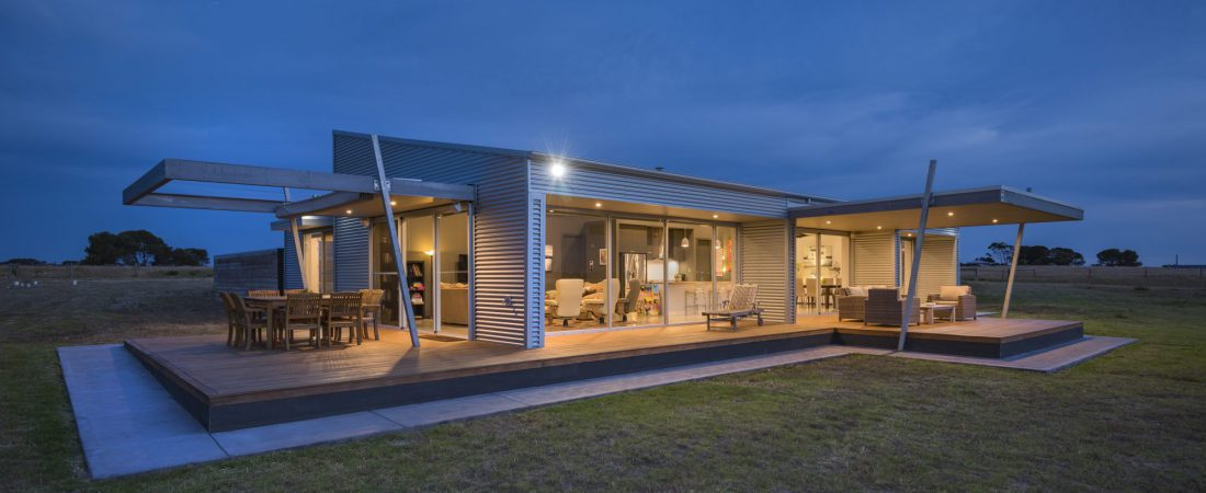 Bespoke home. Outdoors at night, glass wall house with lights on. Open property with large garden.
