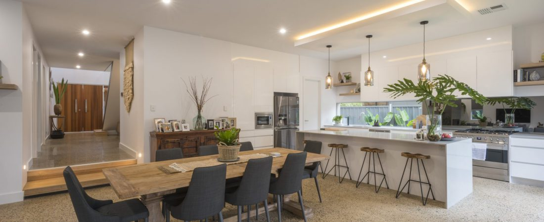 Custom built bespoke home in Kensington, Adelaide. Features dining area, counters and kitchen with lights on.