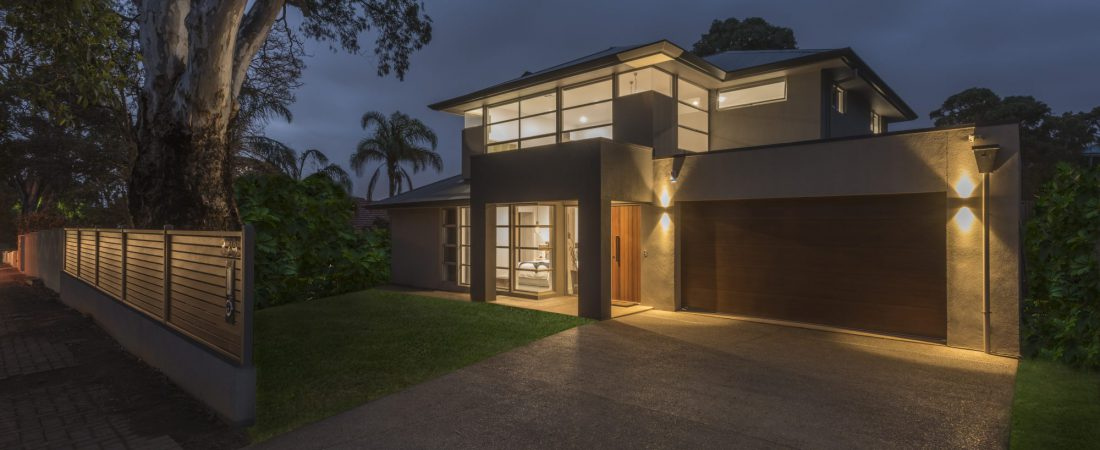 Custom built home in Adelaide at night time with lights on.